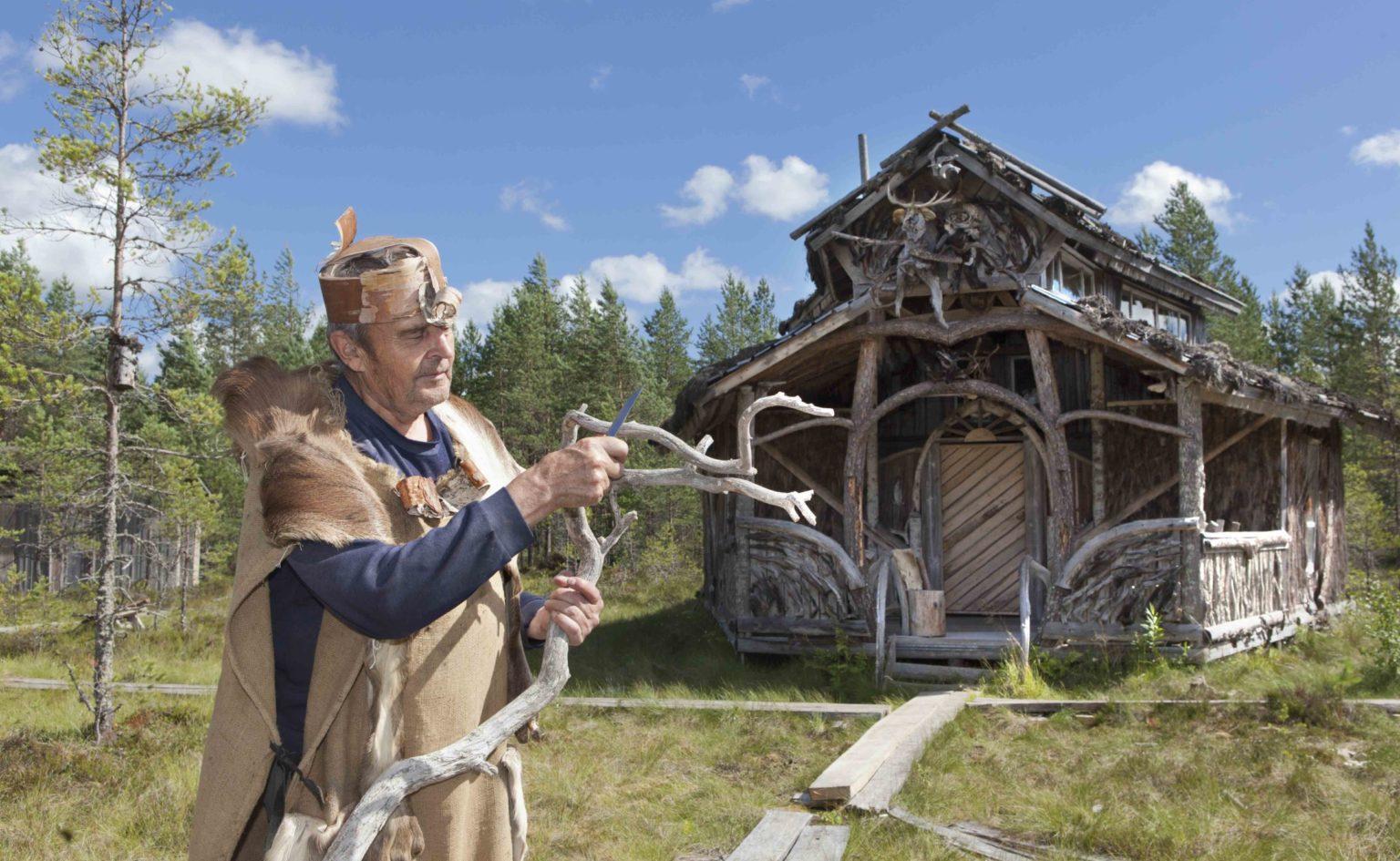 Shamaaniasuinen Erkki Kalliomäki kelopuista rakentamansa erikoisen rakennuksen edessä.