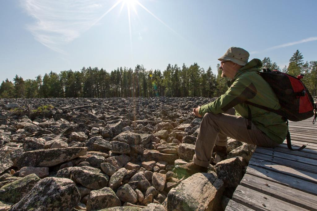 Mies istuu muinaisrannan eli kivijadan yli tehdyllä kävelysillalla