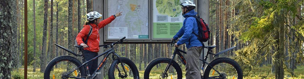 Maastopyöräilijät tutkivat karttaa Kauhanevalla
