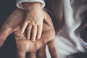 Vanhemman ja lapsen kädet päällekkäin