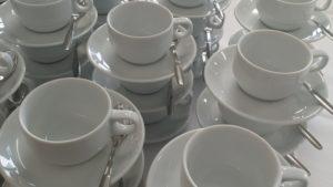 Valkoiset kahvikupit aseteltuna, kuvituskuva.
