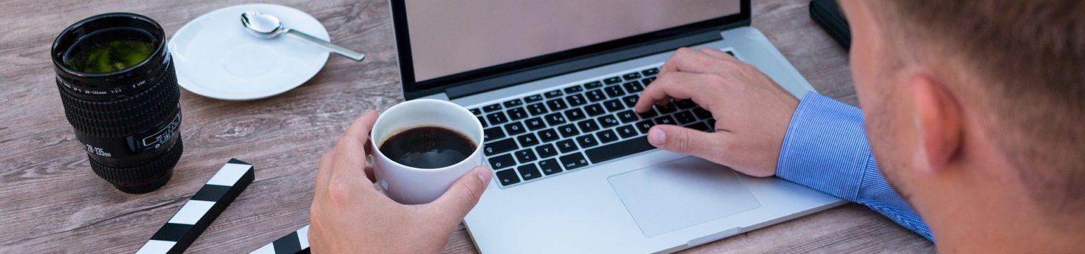 miehen käsi näpyttelee kannettavaa ja toisessa kädessä kuppi mustaa kahvia