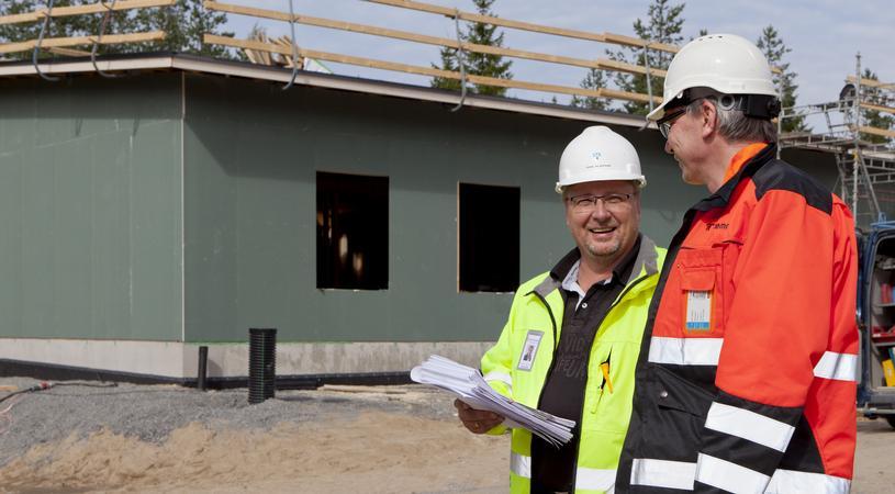 Kaksi henkilöä ja taustalla rakenteilla oleva talo.