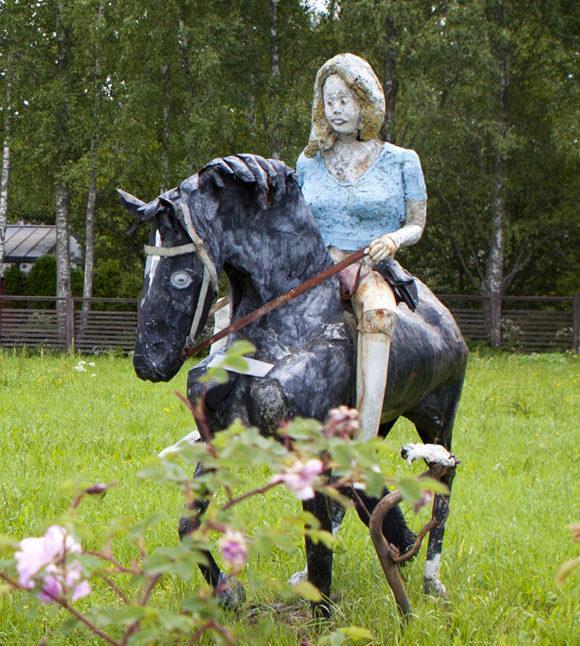 Veistoshevonen ratsastajineen ja lapsia reppuselässä Kotiseututalon puistossa