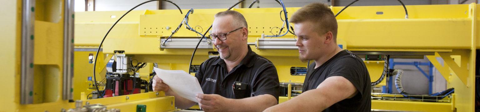 kaksi miestä katsoo jhymyillen piirrustuksia, taustalla keltainen suuri kuljetin