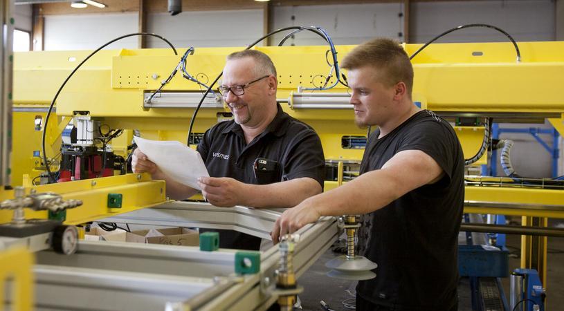Kaksi miestä katsoo papereita tehtaassa.