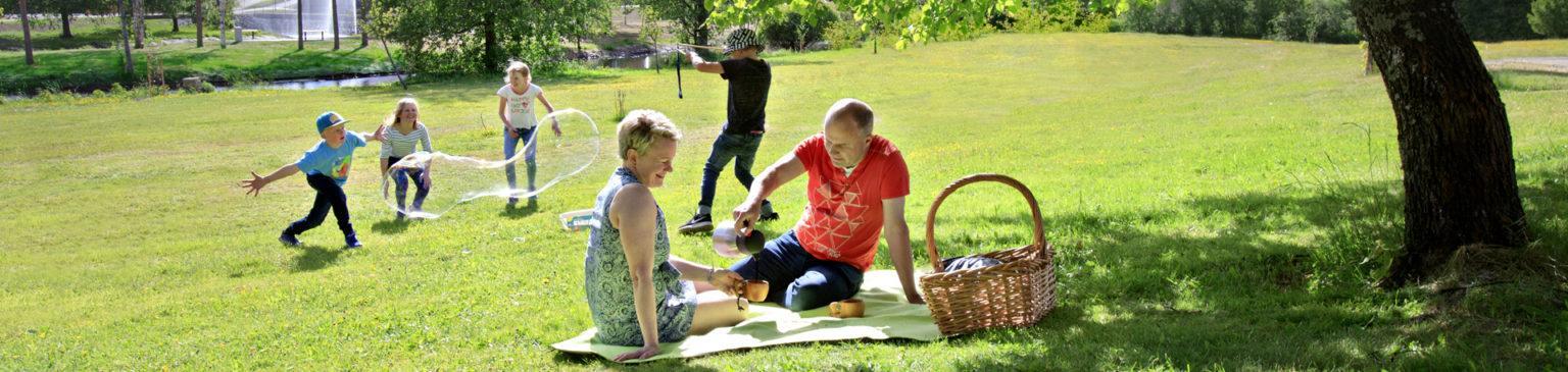 Perhe Jokirantapuiston nurmikolla picknickillä