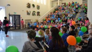 Playcityn päivän päätteeksi järjestettävä kansalaiskokous. Leirille osallistuvat lapset istuvat isoilla rappusilla ja tuoleilla ja leirinjohtaja puhuu heille mikrofonin kautta.