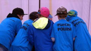 Playcityn poliisit kokoontuneena juttelemaan keskenään sinisissä Playcityn poliisi-t-paidoissa.