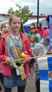 Playcityn pormestarina toiminut tyttö osallistumassa karnevaalikulkueeseen lippu kädessään.