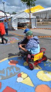 Playcity-lapsia ajaa pienellä pyörästä tehdyllä taksilla.