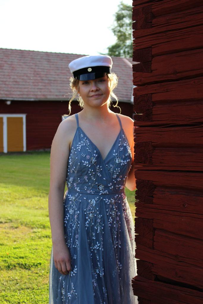 Nuori ylioppilas kuvattuna juhlapuvussaan Hämes-Havusen pihalla.