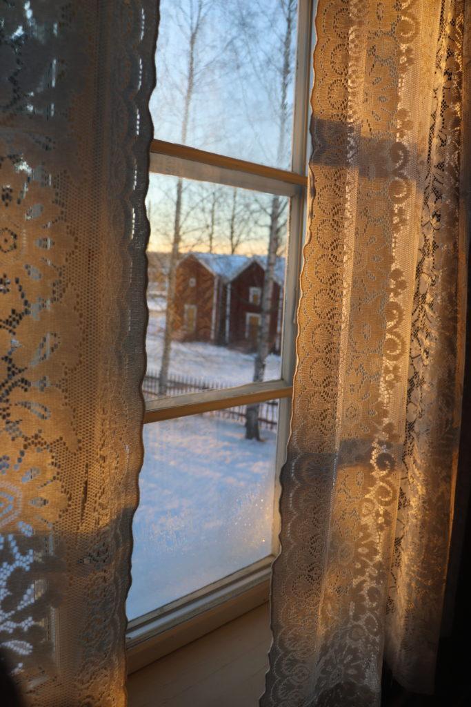 Ulkomaisemaa kuvattuna ikkunan läpi, ikkunan sivuilla vanhat pitsiverhot.