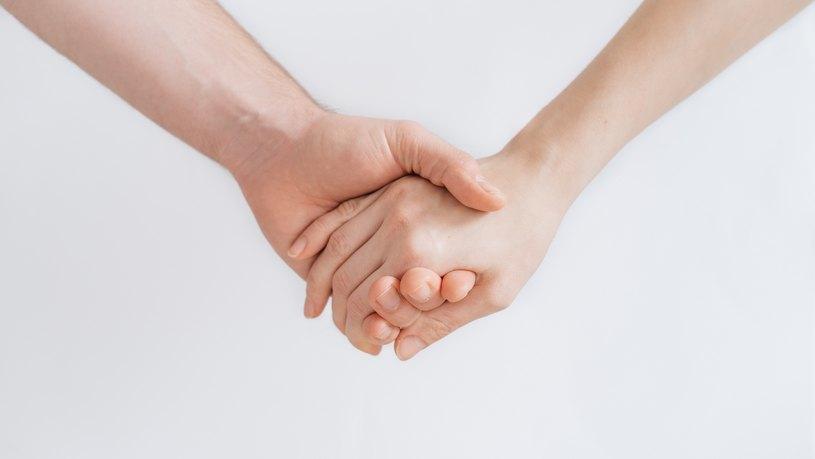 Kahden henkilön kädet pitävät kiinni toisistaan valkoista taustaa vasten.
