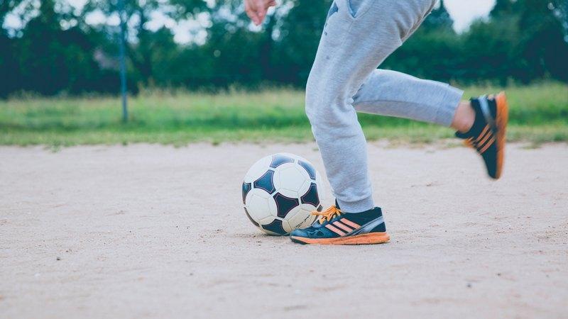 Lähikuva nuoren jaloista potkaisemassa jalkapalloa hiekkakentällä.