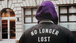 """Ihmisen kuva takaapäin, takissa lukee """"no longer lost""""."""