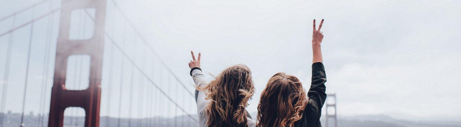 Kaksi henkilöä näyttävät sormilla rauhanomaista peace-merkkiä ja taustalla näkyy Golden Gate Bridge.