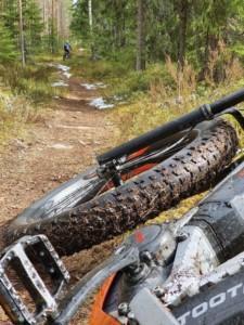 kurainen maastopyörä kallellaan maassa, edessä näkyy keväinen metsäpolku, jossa vielä hiukan lunta siellä täällä ja kaukana edessä näkyy maastopyöräilijän menossa pois päin