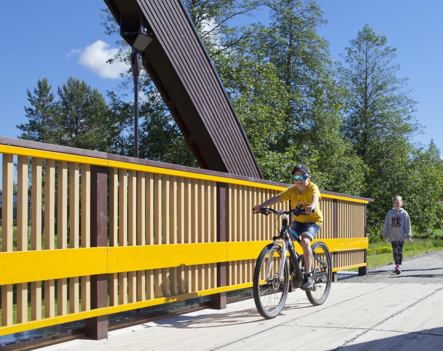 Joen yli menevällä sillalla polkupyöräilijä ja käveliä tulossa siltaa pitkin.