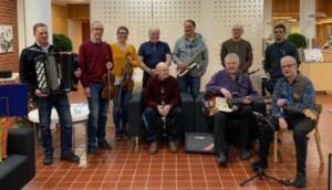 Kauhajoen Pelimannit 2021, kaupungintalon aulassa. Kuusi miestä ja yksi nainen seisoo soittimet kädessä. Kolme miestä istuu soittimet sylissä.