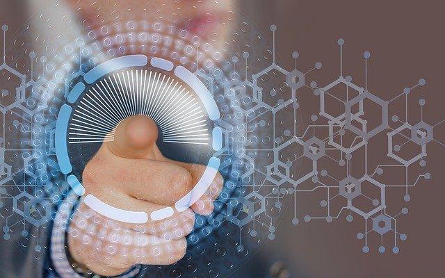 sormi osoittaa kohti katsojaa, sormen ympäriltä lähtee vaalean sinisiä digitaalisia kuvioita ympyrän muodossa, tausta on sumuinen ja ruskea