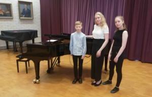 Panula-opiston salissa flyygelin vieressä seisovat pianistit Miko, Moona ja Miisa Viitala.