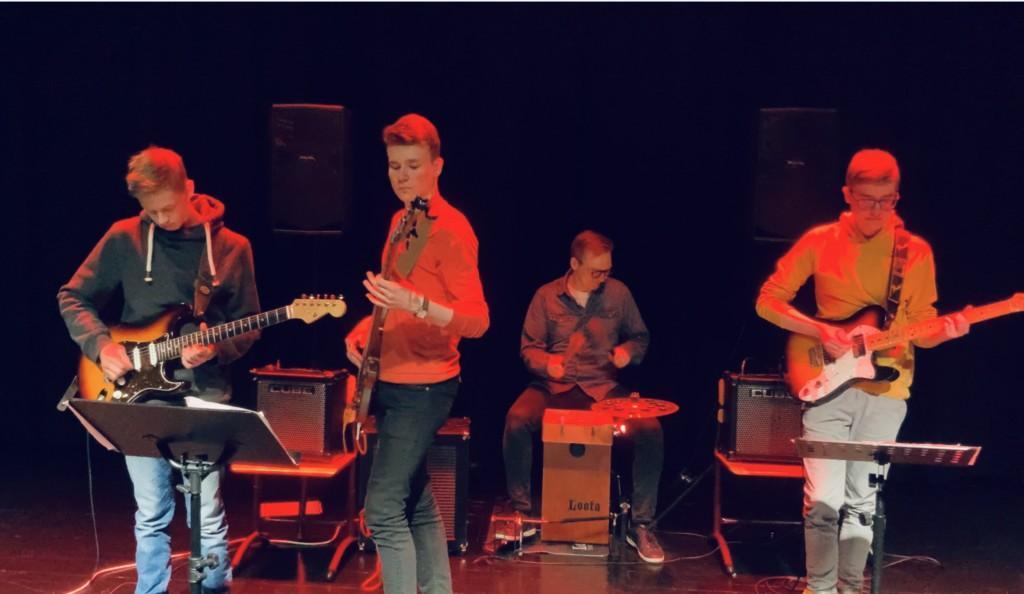 Panula-opiston bändi. Kolme poika soittaa kitaraa ja opettaja soittaa rumpuja.