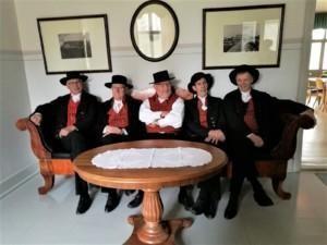 Sorttiset kansantanssiryhma, kuvassa viisi miesta istuu Sanssikartanossa penkillä kansallispuvut (Härmänpuvut) päällä.