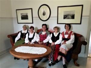 Sorttiset kansantanssiryhma, kuvassa viisi naista istuu Sanssikartanossa penkillä kansallispuvut päällä.