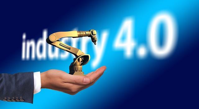 miehen kämmenllä keltainen pieni robotti, tausta sininen ja sumuinen ja siellä teksti industry 4.0