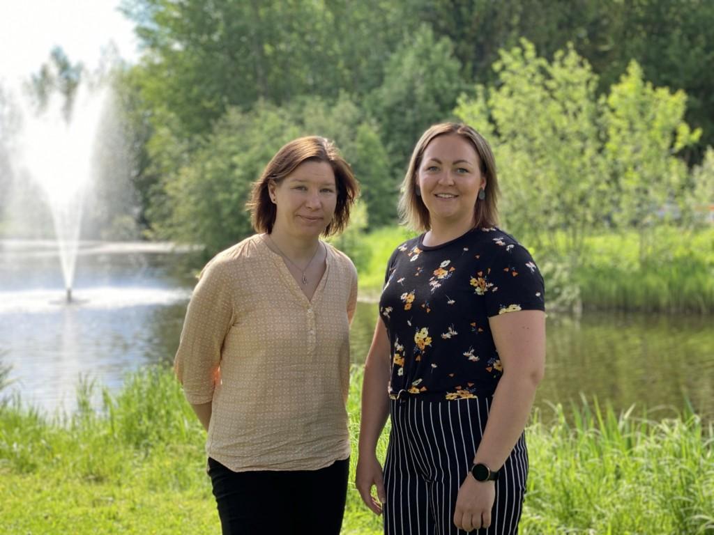 Etsivä Nuorisotyö Kauhajoki,_kuvassa Heini ja Noora seisovat joen rannassa ja suihkulähde taustalla.