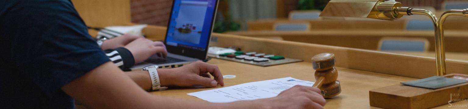 Nuorisovaltuuston puheenjohtaja johtaa kokousta nuija kädessä ja sihteeri kirjoittaa pöytäkirjaa